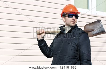 The worker in orange hard hat and sunglasses with a shovel in his hand