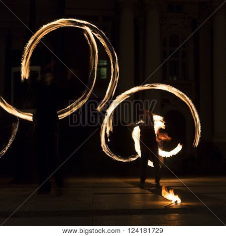 Long exposure square image of an art performer at a fire show in the dark.