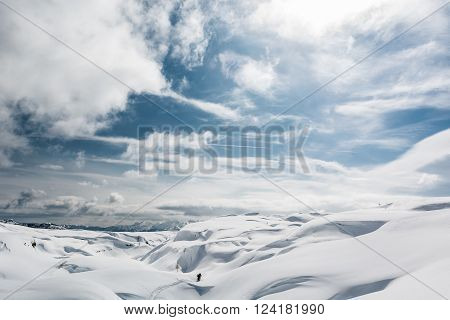 Winter panorama with snow covered slopes and dramatic sky. Komna, Slovenia.
