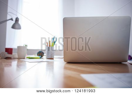 Close up of laptop, cups and papers on the desk