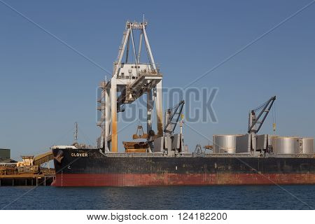 Townsville, Australia - May 11, 2015: Cargo ship is being unloaded at container terminal.