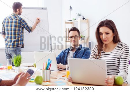Cheerful young creative team is working on new project together. The man and woman are using laptops with concentration. Their male colleague is standing and writing on board
