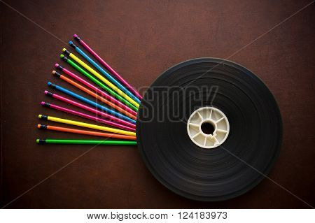 Wooden desktop with colorful pencil and movie film reel