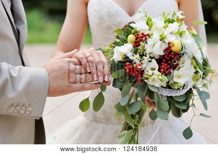 beautiful wedding bouquet at bride's hands and groom