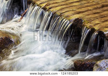 clean water flows through the wooden logs falling cascade down