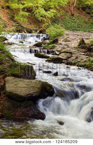 river flows through the stones falling cascade down