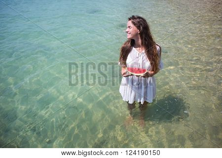Summer portrait of fashion of the surprising healthy sexy woman posing before the blue ocean on the tropical hot exotic island, holding juicy a water-melon, bright flowers,