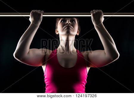 Woman in the gym on black background