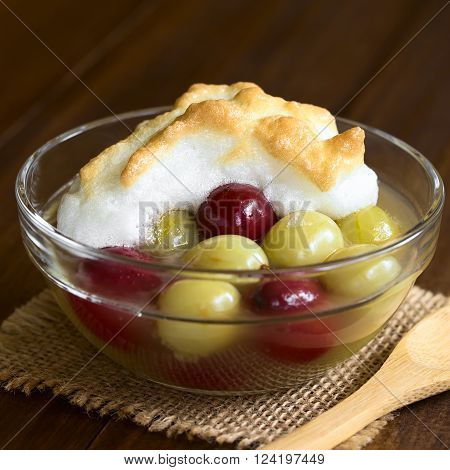 Stewed red and green gooseberry dessert with meringue in glass bowl, photographed with natural light (Selective Focus, Focus on the front of the meringue)