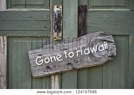 Gone to Hawaii sign on old green doors.