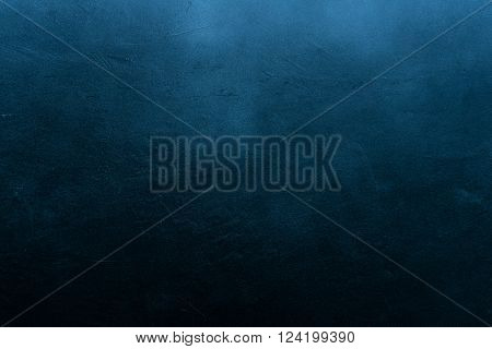 Old scratched and chapped painted dark blue wall. Abstract textured background, empty template
