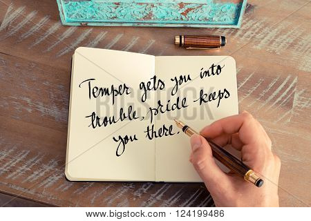 Retro effect and toned image of a woman hand writing on a notebook. Handwritten quote Temper gets you into trouble, pride keeps you there as inspirational concept image