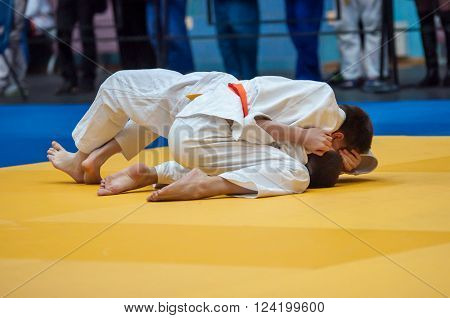 Two judoka in kimono compete on the tatami