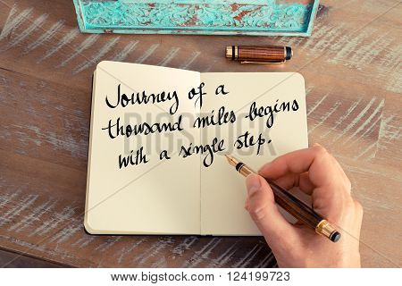 Retro effect and toned image of a woman hand writing on a notebook. Handwritten quote Journey Of A Thousand Miles Begins With A Single Step as inspirational concept image