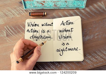 Retro effect and toned image of a woman hand writing on a notebook. Handwritten quote Vision without action is a daydream. Action without vision is a nightmare as inspirational concept image