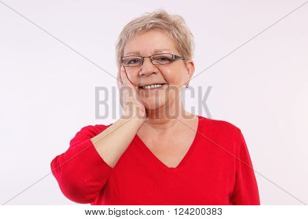 Happy smiling elderly woman holding hand on her face showing positive human emotions in old age facial expressions