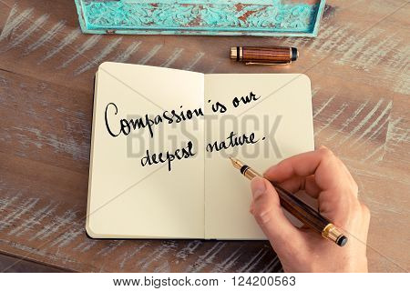 Retro effect and toned image of a woman hand writing on a notebook. Handwritten quote Compassion is our deepest nature as inspirational concept image