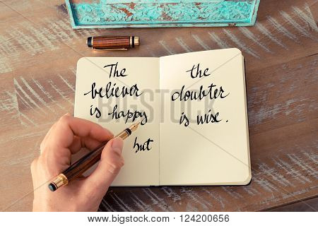 Retro effect and toned image of a woman hand writing on a notebook. Handwritten quote The believer is happy, the doubter is wise as inspirational concept image