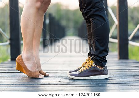 Young couple kissing on wooden walkway, love concept