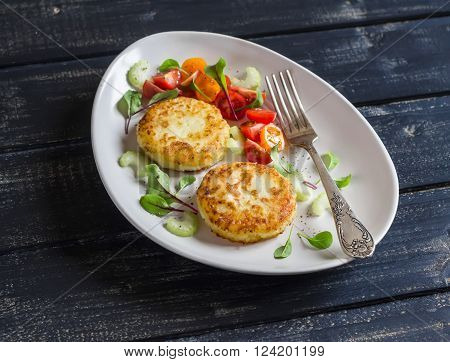 Potato patties and fresh tomato and celery salad on a light ceramic plate on dark wooden background.
