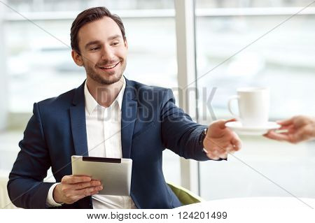 Here you are.  Handsome positive man holding tablet and sitting at the table while getting cup of coffee