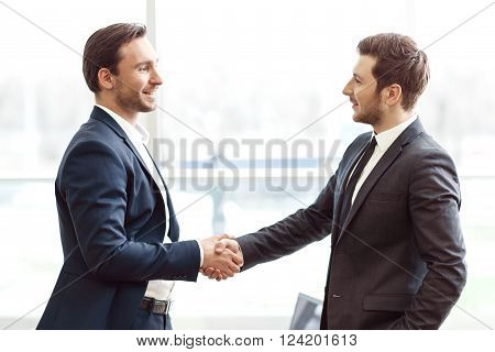 Nice to meet you. Pleasant handsome businessmen smiling and shaking hands while expressing gladness