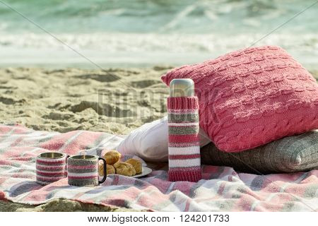 Breakfast on the beach. Coffee and croissants on the sea. Pillows slipcover a thermos bottle and Cup - hand-knitting.