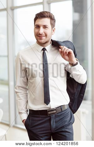 Confidence in mind. Cheerful handsome positive man smiling and holding jacket on the shoulder while expressing joy