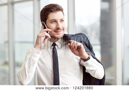 In pace with time. Positive handsome businessman holding jacket on the shoulder and smiling  while talking on mobile phone