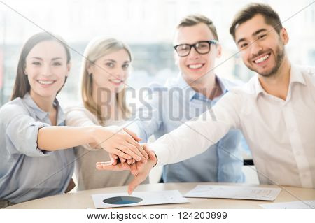 We work in concert.  Pleasant content team sitting at the table and expressing gladness while holding their hands together