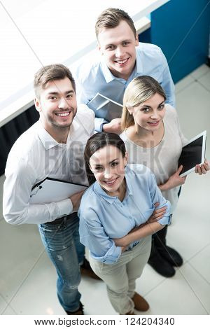 Delighted workers. Top view of cheerful positive professional colleagues standing together and smiling while being involved in work