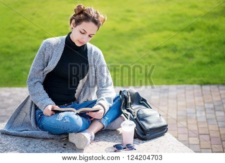 Young beautiful girl reading a book  on outdoors.