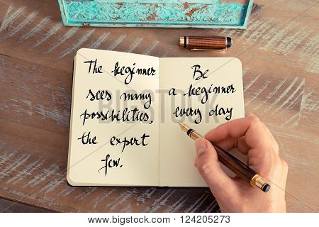 Retro effect and toned image of a woman hand writing on a notebook. Handwritten quote The Beginner sees many possibilities, the expert few. Be a Beginner every day as inspirational concept image
