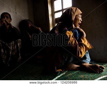 MADURA INDONESIA - November 24 2008: A young female mentally-ill patient screams in a mixed ward at a mental asylum for the poor on November 24 2008 in Madura East Java Province Indonesia.