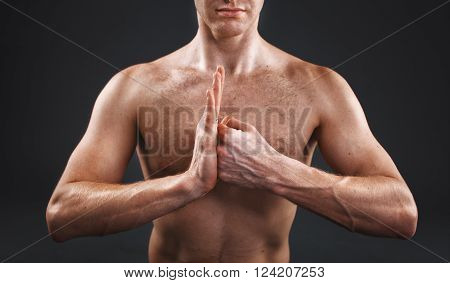 muscular hands clasped yoga master in the studio
