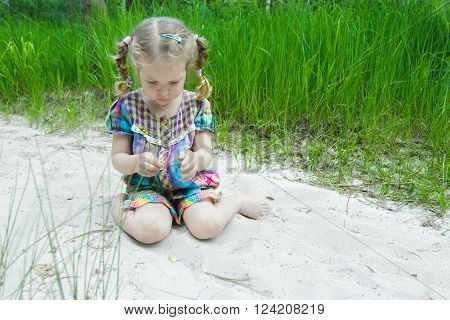Little girl is playing on beach dune and examining little yellow leaf in her hand