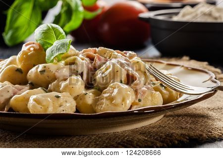 Potato gnocchi, Italian potato dumplings with cheese sauce, ham and basil on a plate
