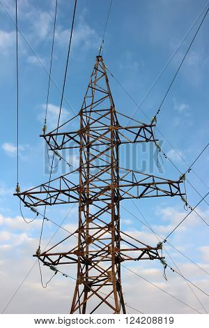 Power transmission tower with wires on a background blue sky and clouds.