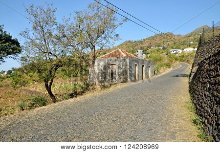 Antique concrete home with red tiled roof by a cobblestone road leading to the mountain side town of Mira Mira in Fogo Cabo Verde