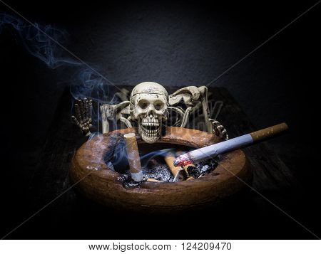 Still life skull and cigarette with smoke.