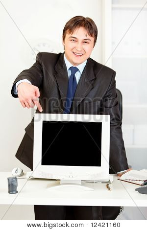 Smiling business man standing behind office desk and pointing finger at monitor with blank screen