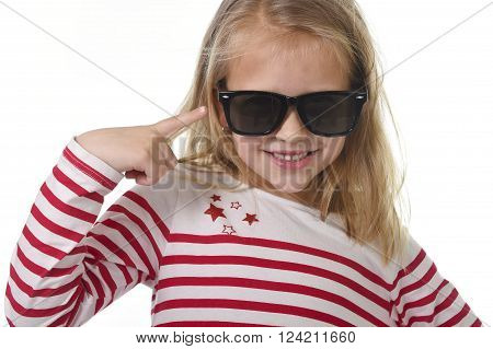 beautiful 6 to 8 years old female child with blond hair wearing red stripes sweater and big sunglasses pointing with her finger happy and playful isolated on white background