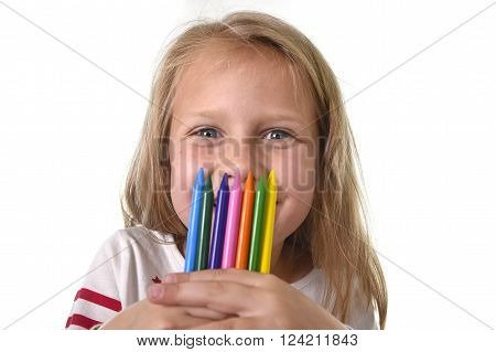 6 or 7 years old beautiful little girl holding multicolor crayons set isolated on white background
