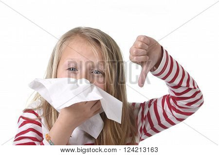 7 or 8 years old sweet and cute blond hair little girl blowing her nose with paper tissue having a cold feeling sick in child winter flu health care concept isolated on white background