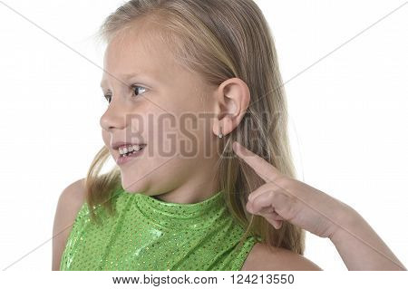6 or 7 years old little girl with blond hair and blue eyes smiling happy posing isolated on white background pointing ear