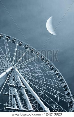 Ferris wheel in the evening at moonlight