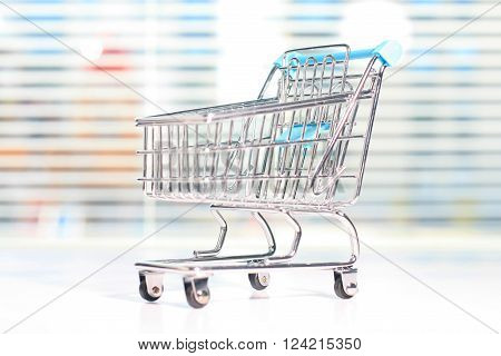 Shopping cart on a white table. Shopping concept.