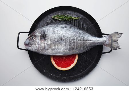 Presentation Of Fresh Sea Bream On Grill Pan Ready To Cook, Isolated In Center Of White Table With G