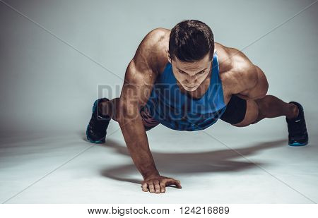 Strong Young Athlete Doing Push-ups On One Hand. Sports Concept