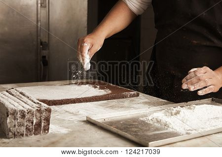 Black Man Chief Pours Sugar Powder On Chocolate Cakes Before Packaging, Professional Artisan Cooking